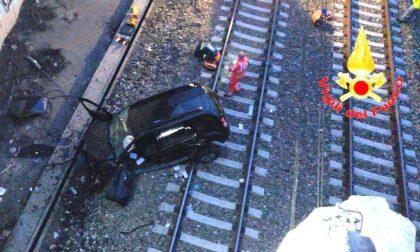 Auto sfonda le protezioni e cade dal ponte sui binari